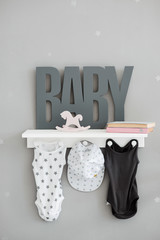 Stylish children's clothing in the room and the words of Baby on the shelf