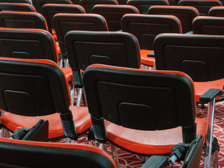 rows of red chairs in empty conference hall