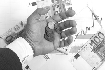 Concept of stock exchange trading profits. Stock market prices charts, 100,50,200 euro bills and calculator on the diagram. Businessman hand in suit with euro cents  coins.Macro black and white image.