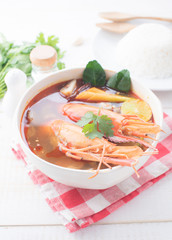 Tom Yam Kung (Thai cuisine) with rice on table wooden