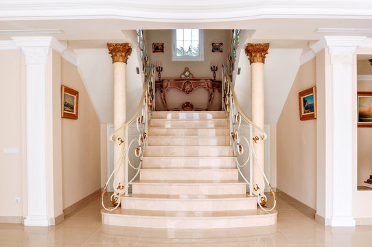 Luxurious staircase with marble steps and decorative and  ornamental iron railings. On the top are decorating furniture in neoclassical style, a table with candles. Corinthian Column Style.