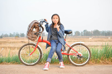 Happy girl with bicycle on grass field, selective and soft focus, concept travel in holiday