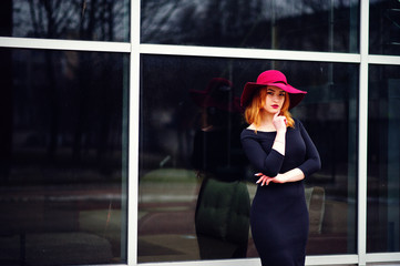 Portrait of fashion red haired girl on red hat and black dress with bright make up posed against large window. Photo toned style Instagram filters.