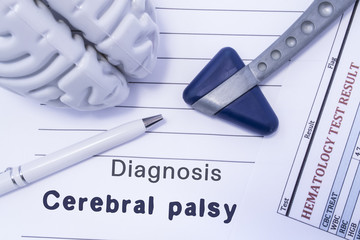 Diagnosis Cerebral palsy. Figure brain, neurological hammer, printed on a paper blood test and written diagnosis of Cerebral palsy in  medical form is lying on table in the doctor neurologist cabinet
