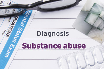 Diagnosis Substance Abuse. Medical notebook labeled Diagnosis Substance Abuse, psychiatric mental questionnaire and pills are on table in psychiatrist cabinet or counselor of this issue or problem