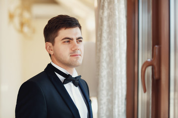 Smiling groom in black suit stands in the rays of morning sun before the window