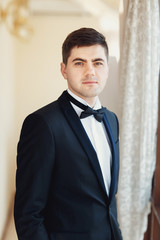 Portrait of handsome young groom standing straight in the room