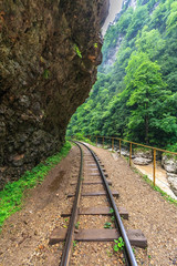 Beautiful scenic vertical landscape of vanishing narrow-gauge railway tracks passing through Guam river canyon in Caucasus mountains at summer, Russia