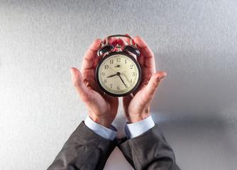 patient businessman hands holding an alarm clock for time management