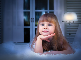 child on bed before going to sleep. Portrait of a little girl