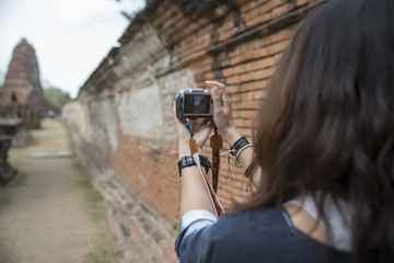Beautiful woman holding mirrorless,take photo at Ayutthaya historical park,Thailand.