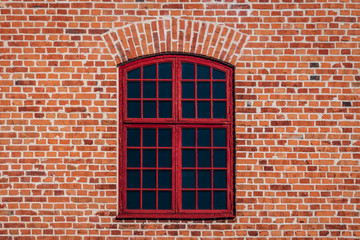 Brick wall from old building with a large red window with cross bars