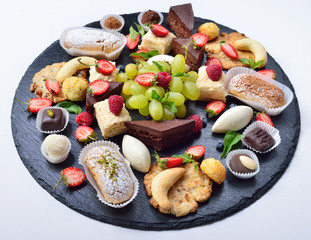 Assorted sweets, lot of sweets, cakes, fruit and chocolate on a slate base. Isolated. The concept for a restaurant.