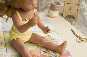 Doll in yellow suits with metal hanger is on the opened book.