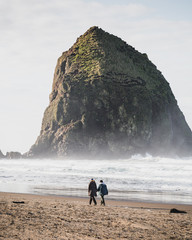 Couple walking on the coastal beach near Haystack Rock