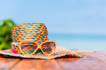 sunglasses and straw hat with blur blue sea and sky background - holiday concept
