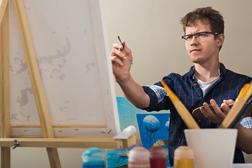 The man draws a picture. The man nursed drawing. The artist draws a picture.