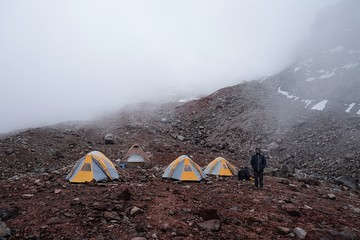 Person Standing By Tent On Mountain In Foggy Weather