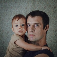 Portrait Of Father And Son Against Wallpaper At Home