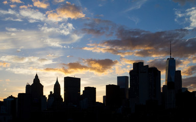 New York City Skyline Silhouette at Sunset with Colorful Clouds in Background