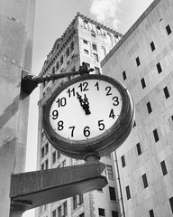 Downtown street clock at a few minutes before twelve