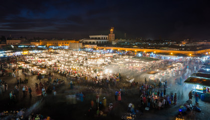Famous square Jemaa El Fna busy with many people and lights during the night, medina of Marrakesh, Morocco