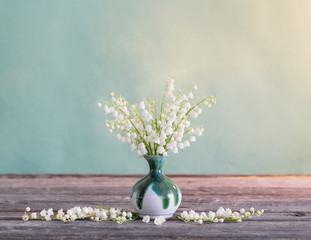 Lilly of valley in vase on wooden table
