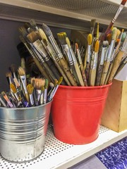 Art Studio. Many dirty brushes in red and silver buckets.