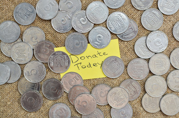 A lot of coins lying on the background of burlap with a label with the words for a donation today. Ukrainian coins. Sacrifice. To help. Do not be indifferent