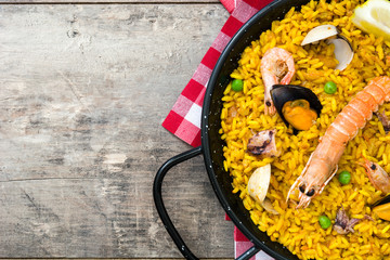 Traditional spanish seafood paella on wooden background.Top view