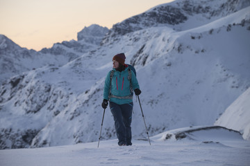 Female hiker in winter mountain landscape, Ytresandheia, Moskenesøy, Lofoten Islands, Norway