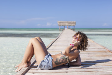 Western tourist girl using her smartphone on a beautiful beach in Cayo Guillermo, Cuba