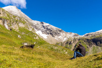 Ein Mann fotografiert eine Kuh vor dem Bergpanorama