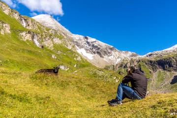 Ein Mann fotografiert eine schwarze Kuh vor einem Gipfel