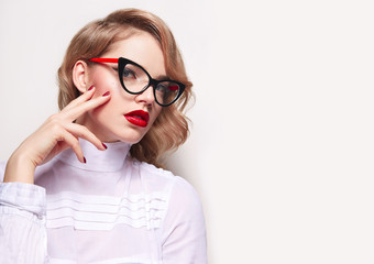 A girl in retro glasses with diopters with red lipstick red nails smooth skin and a beautiful retro hairdo in a white blouse sits.