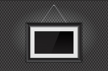 Photo frame hanging. Black rectangle with wide border on metal perforated background