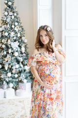 Pregnant girl in a dress in a New Year's interior