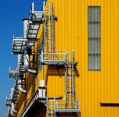 Smoke stacks and safety ladder of a yellow factory