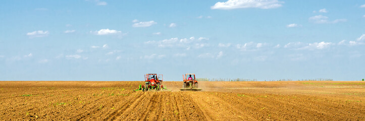 Tractors sowing on agricultural fields on beautiful sunny spring day