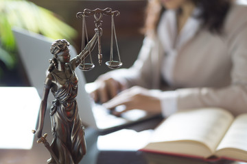 Statue of Justice and lawyer working on a laptop