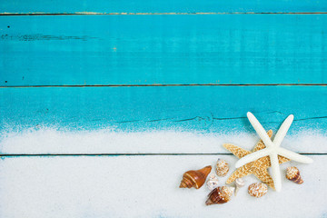 Seashell and sand border with teal blue rustic wood background