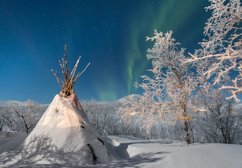 Northern lights and teepee in snow, Finland