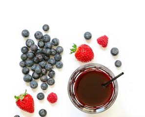 A glass of strawberries, raspberries, blueberries juice isolated on white.