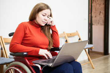 Portrait of Caucasian woman in invalid wheel-chair working with laptop on knees, disabled person