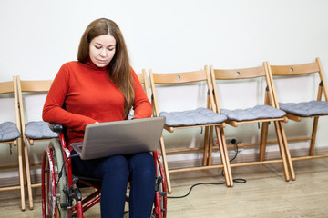 Beautiful Caucasian disabled woman sitting wheel chair and works with laptop indoor