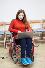 Woman in invalid wheel-chair working with laptop on knees, disabled person