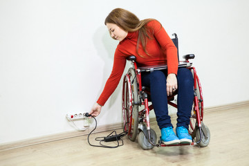 Disabled Caucasian woman in wheelchair stretching to power socket in wall for turn on laptop