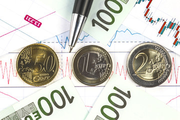 Concept of European stock market exchange trading. Hundred euro bills, fifty euro cents, one euro coin and two euros coin on the stock market graph. Red line on the chart. Black pen. Macro image.