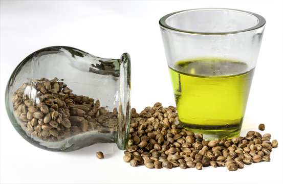Hemp seeds and hempseed oil in a glass beaker on a white background. Selective focus.