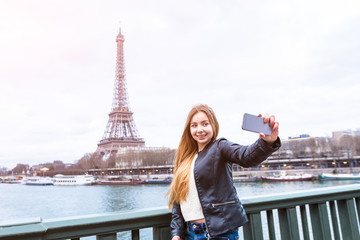 Tourist girl taking selfie in front of Eiffel Tower, Paris